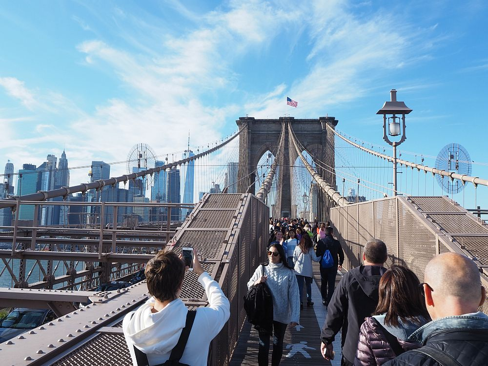 The walkway leading to the first tower, with the Manhattan skyline, partly obscured by the bridge structure. Straight ahead: the walkway/bike path, filled completely with people walking across the Brooklyn Bridge in both directions. The cables rise in a slope from this point up to the top of the support tower. A man in the foreground takes a picture with his phone.