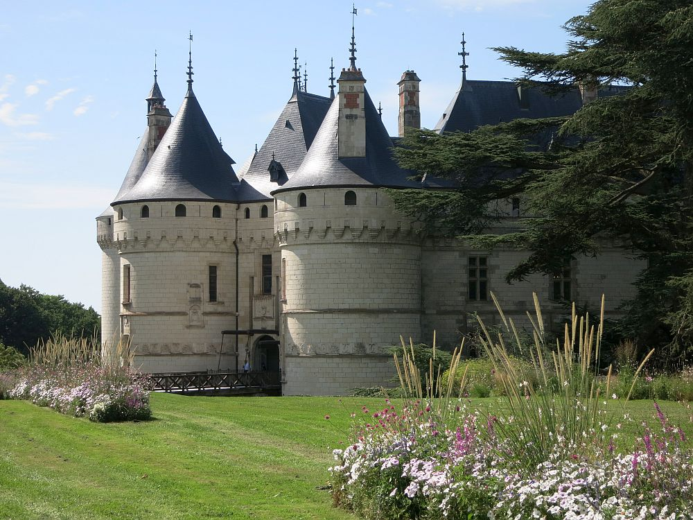 The castle has a rounded tower on each side of the entrance, and each tower is topped with a pointed grey turret.
