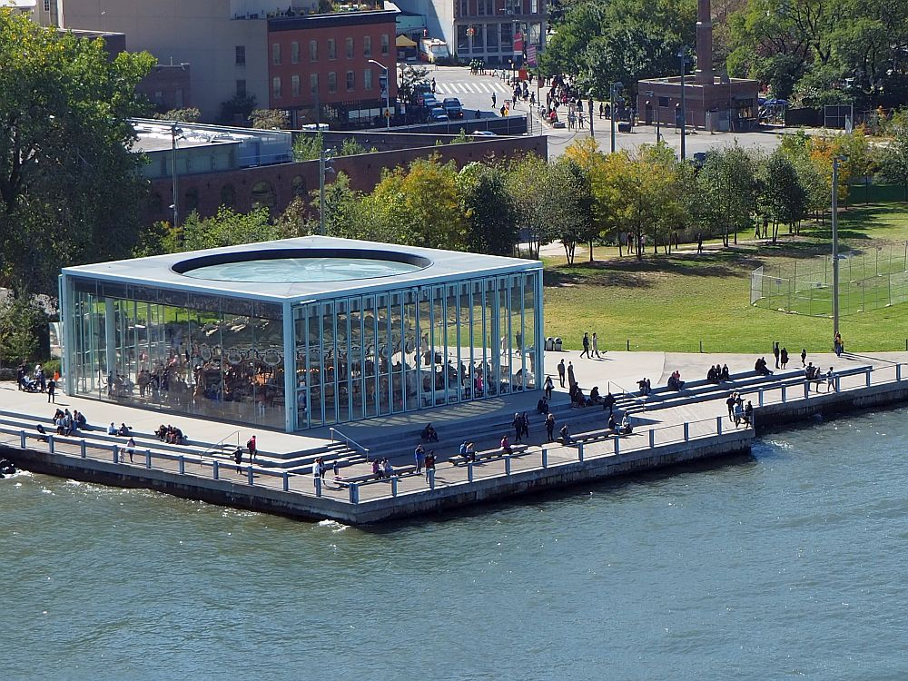 Seen from above and at an angle, Jane's Carousel is housed in a squat, square glass building. The carousel is visible inside through the glass. The river's edge parallels two sides of the square building, and the space around the building is paved, with a small fence along the water's edge.