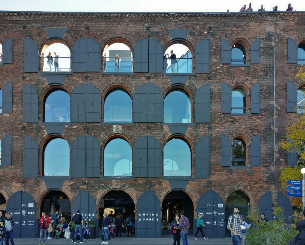 The building is red brick and five stories tall. The bottom three stories have arched glass windows with black shutters that are open against the building. The fourth floor has the same arched windows, but they have no glass, just a railing, and people stand, looking at the view. A fiew people are also visible on the fifth floor, i.e. the roof, looking at the view.