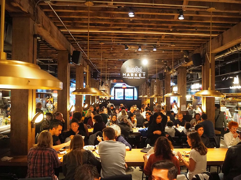 On the left and the right, food stands line the room. Down the center, long horizontal tables fill the space: perhaps five rows of them in this photo. All the seats are filled with people eating.
