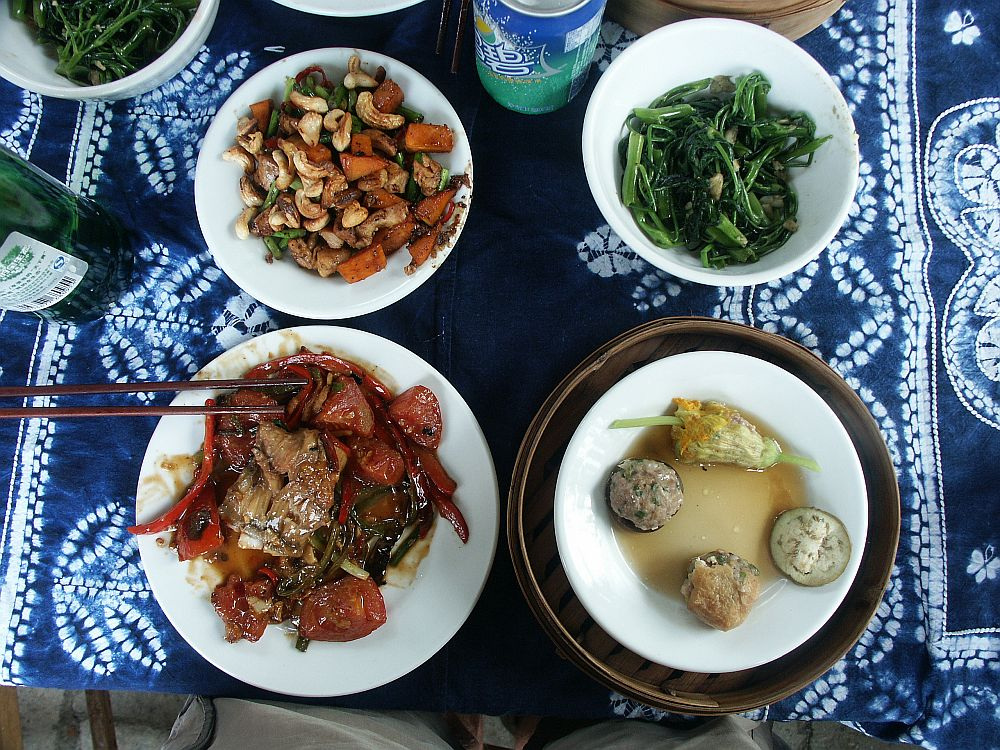 Four dishes, seen from above, on a blue and white batik tablecloth. Top left, chicken with cashew nuts. Top right: some sort of greens. Bottom left, beef, I think, with red peppers and tomatoes. Bottom right: three small dumplings, all different, and a fourth one that is a stuffed flower.