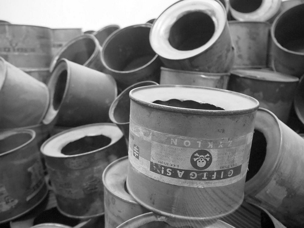 "Black and white picture of a pile of empty cans of Zyklon B. Each is round, and one end has a large hole in the center. The nearest one is legible: ""Giftgas! Zyklon"" with a skull and crossbones symbol."