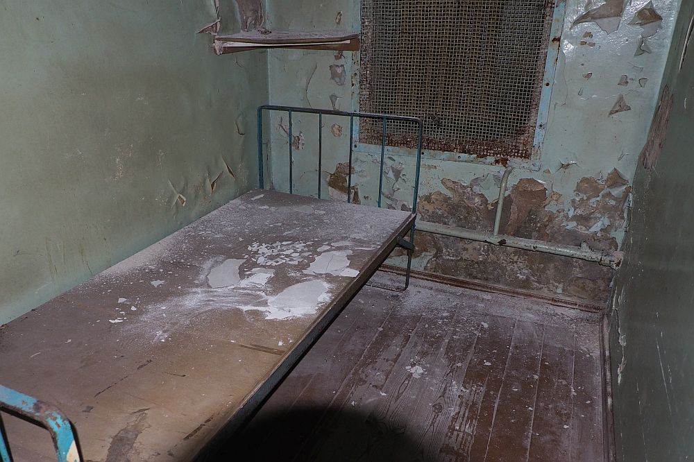 A bare bed on the left, without a mattress and with barred head and food boards. It looks like someone spilled plaster or something onto the bed. The wall beyond has peeling, rusty-looking greenish paint. The window is covered with some kind of mesh. The floor is bare boards.