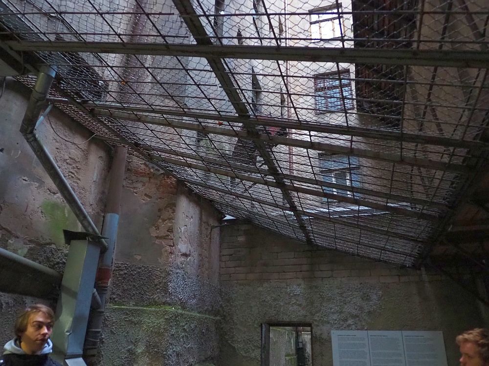 This view looks slightly upwards: the roof cage is broad bars, quite far apart, with chain link fencing on top of that. Two concrete or brick walls can be seen in this picture, and looking through the roof bars a vertical row of windows up the building.