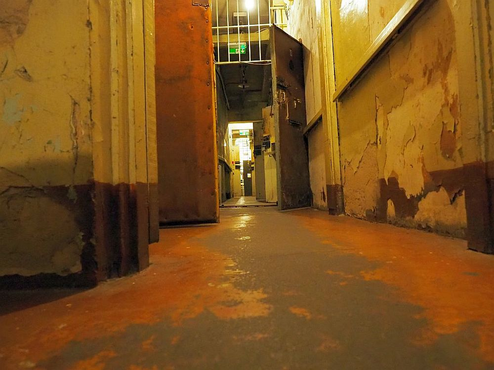 Looking down a hallway, in the middle distance is a door, open, with a heavy lock and bars above it to the ceiling. Beyond that are more open doors on the right with heavy locks. The paint has worn off the floor except on the edges. Along the right-hand wall of the hallyway is a horizontal bar.