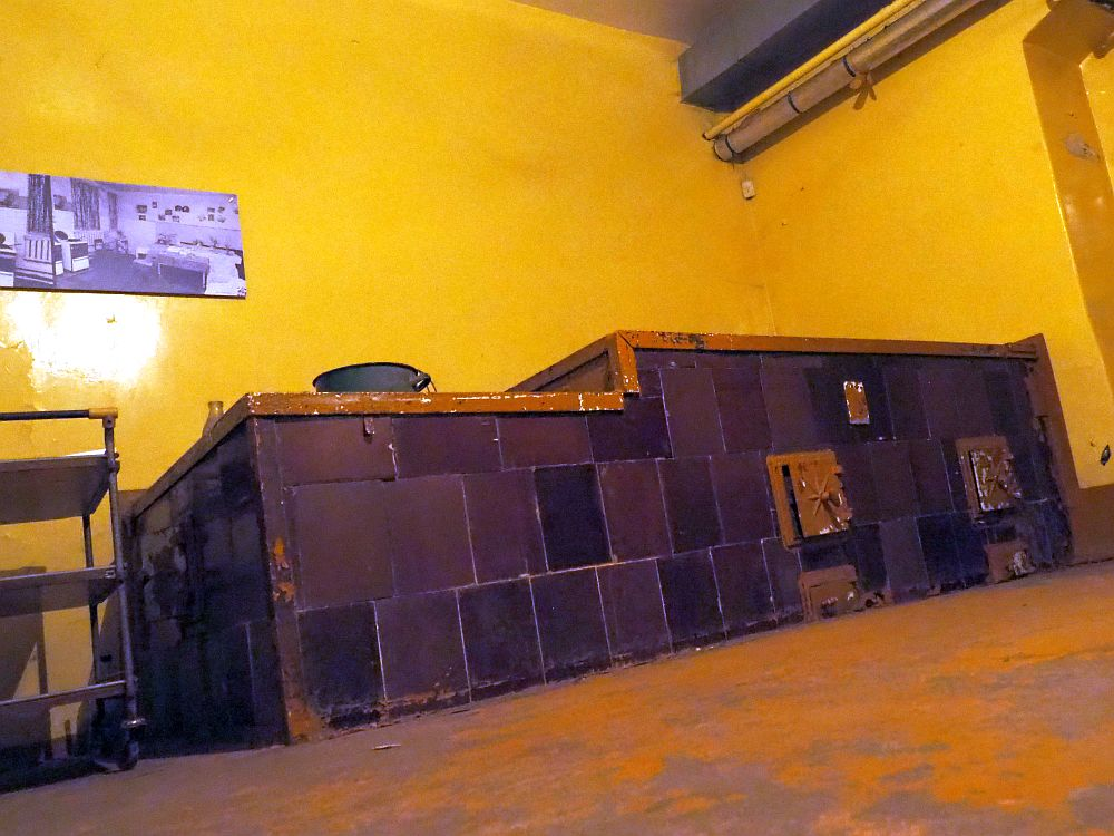 Photo taken from floor level. The stove is built into the wall, a large, two-level box, covered with dark brown tiles on the sides, and with two hatches in the side for inserting wood into the fire. The wall behind it is yellow. In the photo on the wall, there are two modern white stoves, the kind with gas burners probably, and white sides.