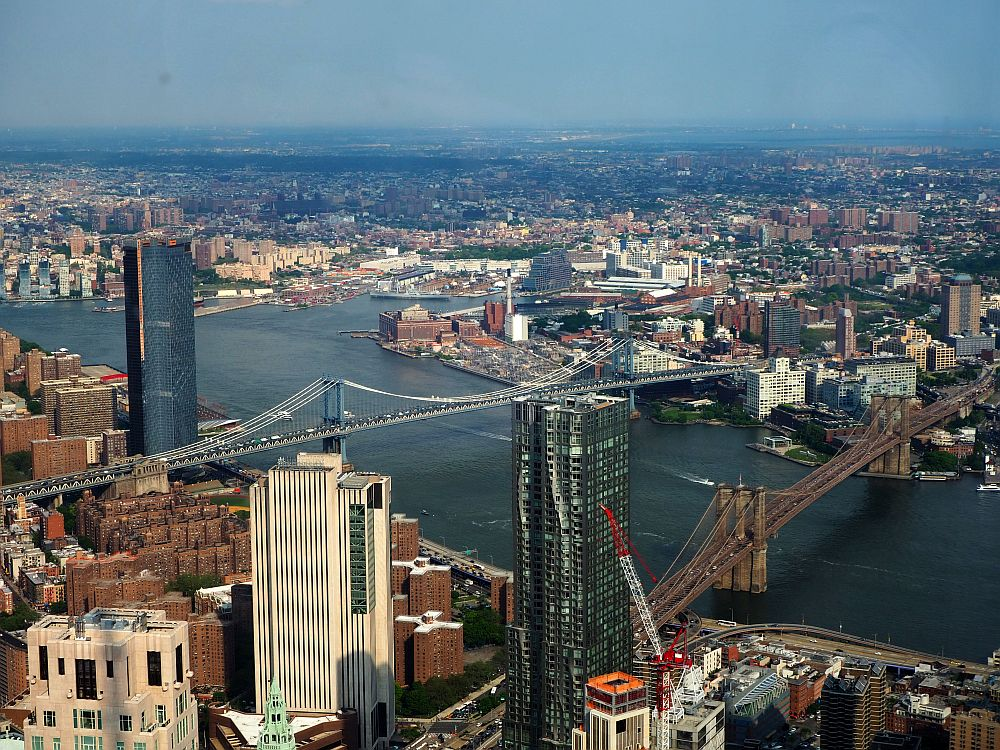 The river cuts through the picture diagonally, with the two bridges, both suspension bridges, crossing it. the rest of the picture is filled with a city view of lots of buildings of various sizes.