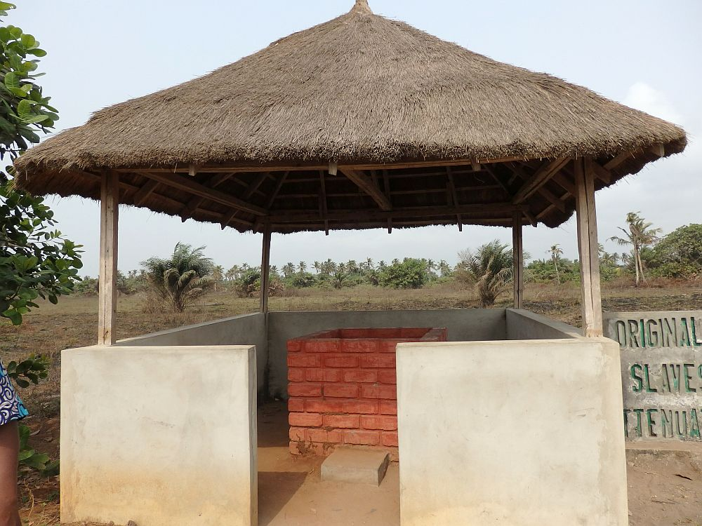 The well itself is square and walled in red bricks. Around that is another square of walls, plastered in white and open on one side enough for a person to enter and reach the well. The white square of walls has a pole in each corner and those poles hold up a square thatched roof.