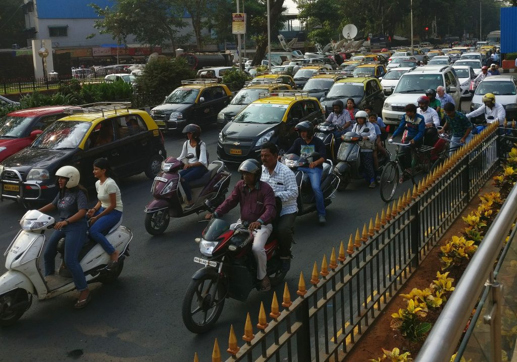 A very full roadway, with, nearby, a group of motorcycles, some carryign two people. Only some of them wear helmets. The rest of the traffic appears to be cars and taxis, and they're not moving, judging by the fact that the motorcyclists in the foreground have their feet steadying their motorcycles.