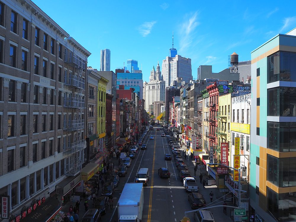 A view down a Chinatown street from the Manhattan Bridge. Multistory brick buildings line the sides, some painted in bright colors, traffic down the center. Shop signs in Chinese.