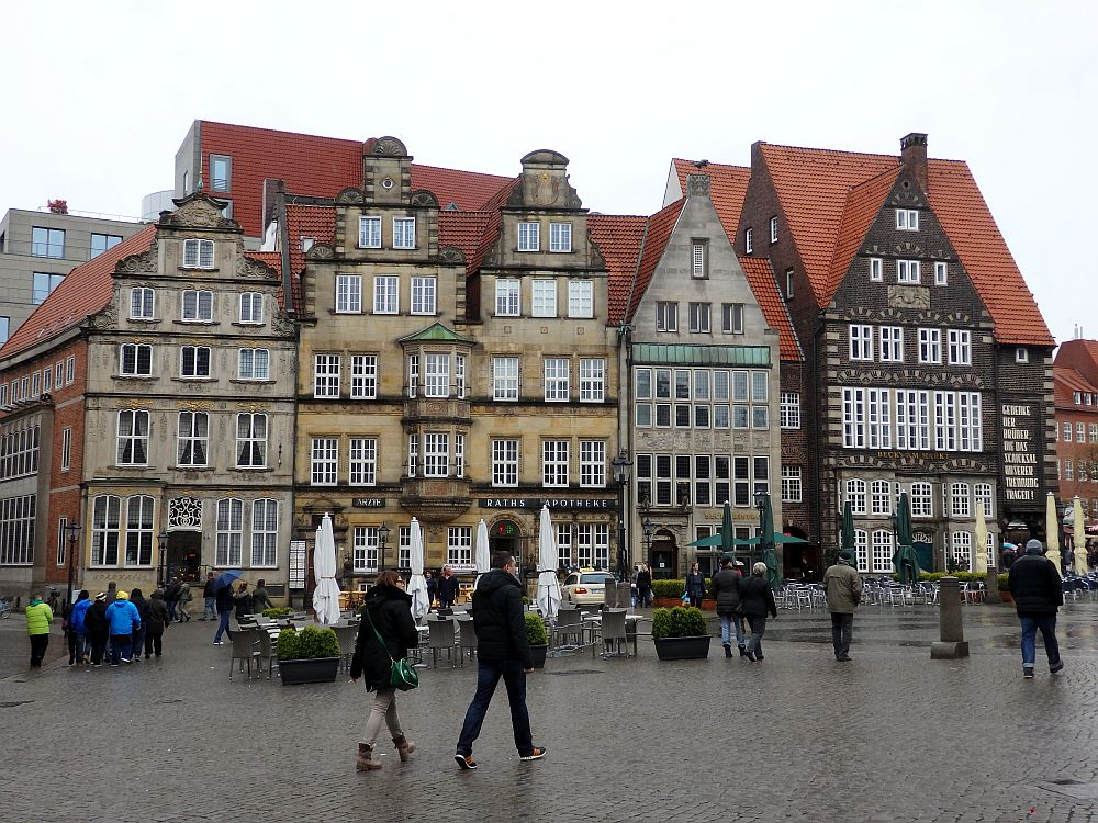 A row of buildings, all in shades of brown with red roofs. Some have stepped roofs, some simpler points. All have a lot of windows. In front of them are tables and chairs for an outdoor cafe, but it's rainy and no one is sitting there. People are walking by.