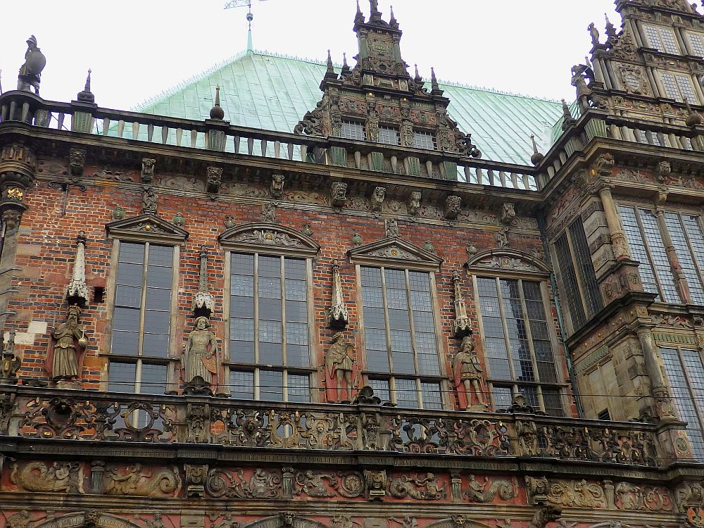 The building is red brick. The balcony has an ornately carved railing and the wall behind the balcony has a row of tall paned windows with statues between each two.