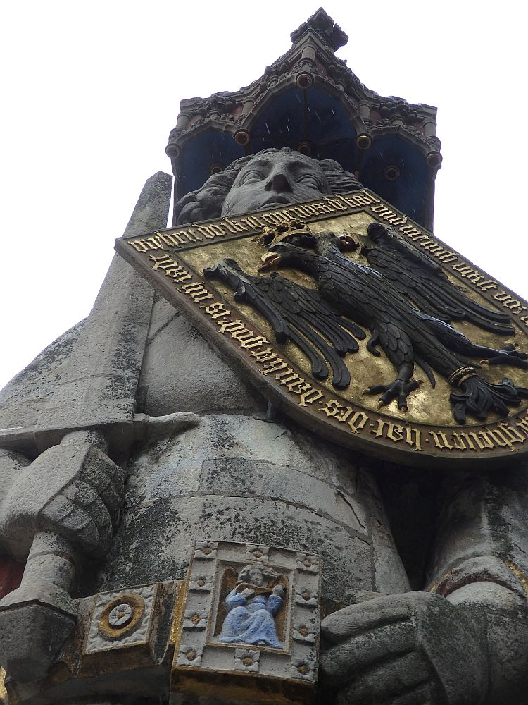The statue is seen from below in this photo. The figure of a man (I think) holds a sword in one hand and has a shield across his chest showing a double-headed eagle on a gold background with gold words around it. His belt buckle portrays a woman (I think) ina blue robe, playing a lute or mandolin or similar.