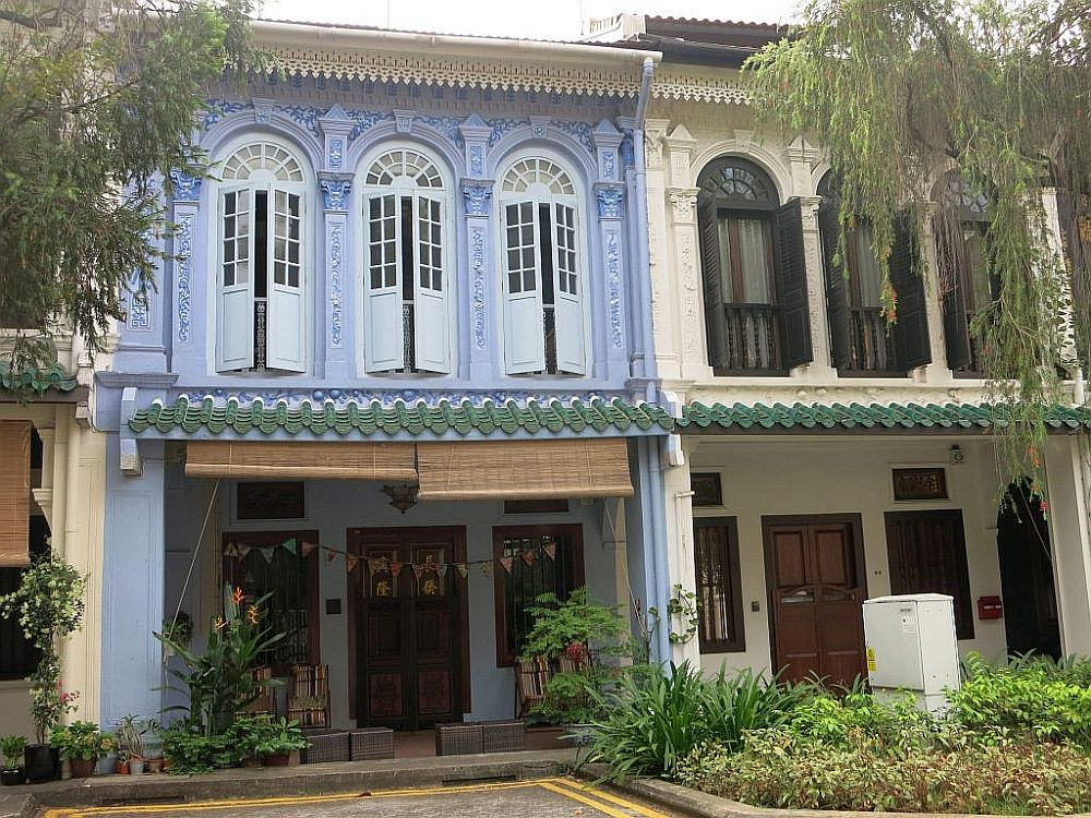 Two row houses in Singapore: each is two stories high, with the ground floor shaded by a small roof. The upper floors are quite decorative, with tall windows with shutters and arched windows at their tops, and ornate decorative elements between and above the windows. The left-hand house is predominantly a pastel purplish-blue and the right-hand house is beige with brown edging and shutters. I think Singapore would be a great place to live as an expat.