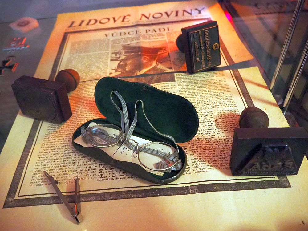 "The newspaper underneath is in Czech, titled ""Lidove Noviny"". The article's title is ""Dudce Padl"" and the only photo of the page is of Hitler. On top of the paper is an open glasses case with small round wire-rimmed glasses, three stamps and a tie pin."