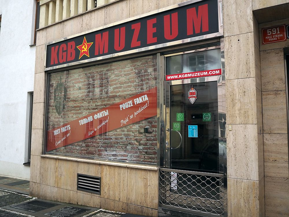 "The store front reads ""KGB Muzeum"" with a red star with a hammer and sickle inside it. The store window appears to be bricked up."