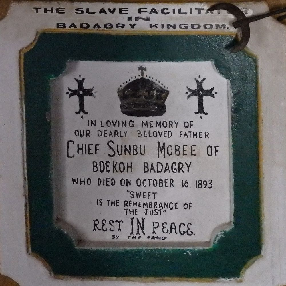 "A plaster sign, white with a green frame around it. Above the sign it reads ""The slave facilitator in Badagry Kingdom."" and inside the frame it reads, under a picture of a crown and two crosses: ""In loving memory of our dearly beloved father Chief Sunbu Mobee of Boekoh Badagry who died on October 16 1893 ""Sweet is the remembrance of the just"" Rest IN Peace. By the family"""