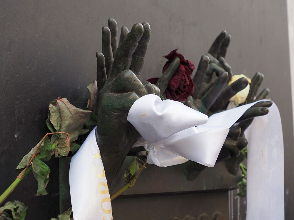 A metal plaque on a plain background. The cluster of hands emerges from the top of the plaque: about 7 hands, some showing the V sign with palm outward, some showing all fingers with palm outward. A white ribbon has been wrapped around some of the hands and obscures them, along with a shrivelled rose. It emphasizes the peaceful nature of the protests that started the Velvet Revolution against the communist leadership in Prague.