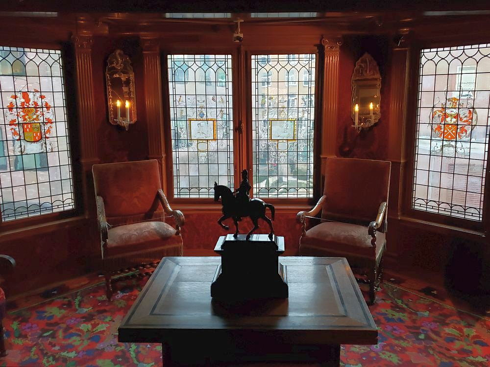 A square dark wood table stands in the center of the room, with a small pedestal in its midde, holding a statue of a man on horseback. The floor has a dark red, flower-patterned carpet. Beyond the table are two simple dark red armchairs. Between them, two paned windows and one window on either side of them as well. The four visible windows have small panes that have been painted. The paintings in the middle two windows (in a picture at the beginning of this article describes one of them) are hard to see, but the two one either side are painted brightly: on the left, a vase with bright orange flowers. On the right, a coat of arms, also in orange.