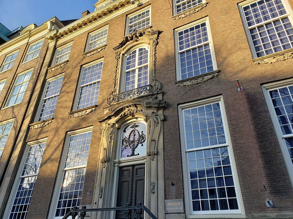 Like many Golden Age houses in Amsterdam, the facade is relatively plain but with very large windows: more window space than walls between. The wall is red-brick. A simple ornamental piece below each window, but otherwise they're plain. The center, though, has the main doorway, surrounded by decorative stonework. The window directly above the door is also framed by decorative stonework, with a small frilly, metal railing along the bottom.