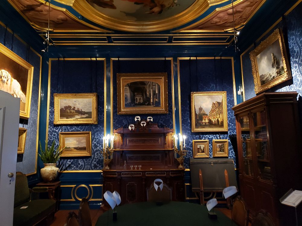 The walls of the parlor are covered with a royal-blue velvet paper. The edging is gold, as is the ceiling. A small part of the central painted ceiling is visible. On the wall panels is a collection of Golden Age paintings, each framed in gold.