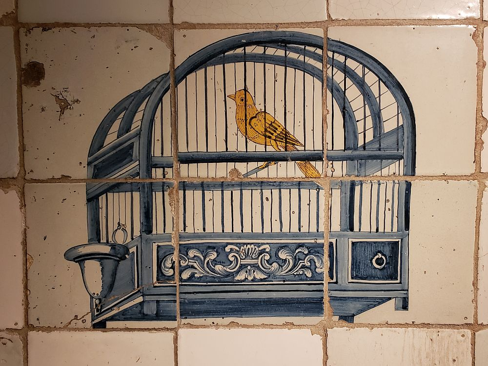 Covering a space of six tiles, the image is of a blue bird cage, quite simple, holding a single yellow bird. Other than the image, the tiles are white and a bit chipped around the edges.