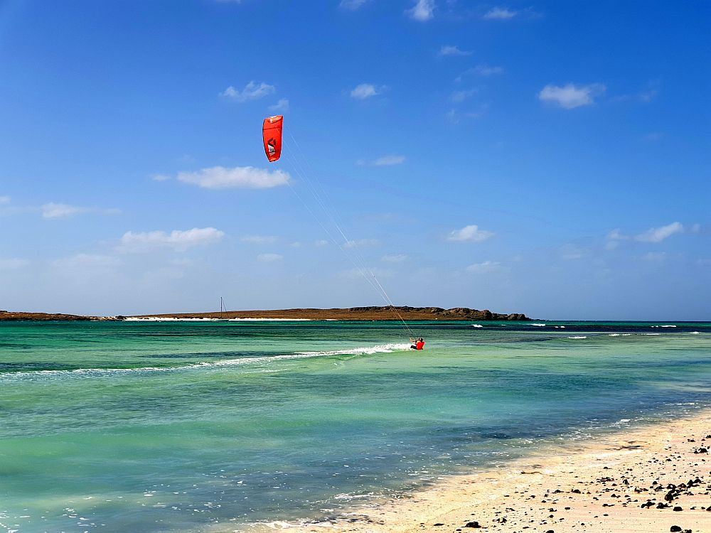 A man is leaning (perhaps falling) in the shallow water near a beach. His kite nearly above him is bright red.