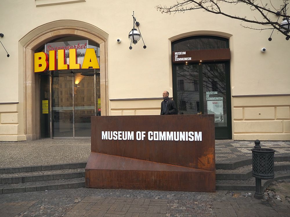 "A plain metal sign reads ""Museum of Communism"". Behind that is the simple entrance to the museum. To the left of the entrance is a bigger arched door, with big letters proclaiming ""BILLA"": the entrance to a supermarket. One man, my husband, stands in front of the museum entrance, waiting for me to finish taking pictures."
