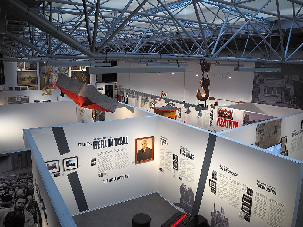 "The space has a high roof with a latticework of bars holding up a translucent glass ceiling. Below, the walls around the exhibit spaces are normal wall height but without ceilings, so from this viewpoint the contents of the rooms are visible. The nearest room has titles painted on the wall that read ""Fall of the Berlin Wall"", ""Dissidents"" and ""Normalization."" The rest is not legible form this distance."