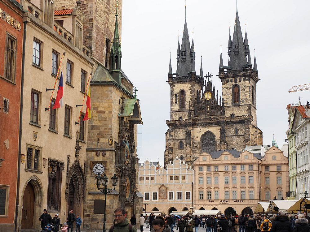 On the left is the famous astronomical clock, built onto the side of a building. In the background, across a big open square, is a row of buildings, about 6 stories high, all in shades of beige. Behind them and much taller: a large cathedral with two spires, each adorned with a number of smaller turrets. At least the communist rulers of Prague left the old section intact.