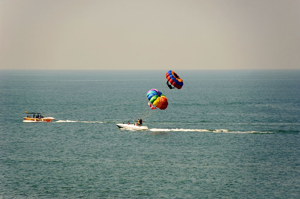 In this phot are two boats. The one in the center has two parasails in the air above it, or perhaps the boat to the left is pulling one of them. It's hard to tell. Both boats appear to be moving, but not very fast, and the parasails are multi-colored.