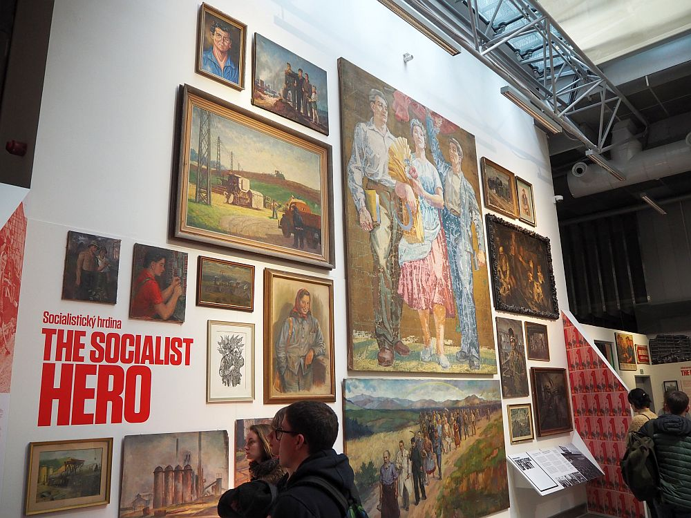 "The wall is about two stories high and is covered with artworks, mostly showing things like proud peasants and workers in idealized country settings. A few people at the bottom of the photo look at them. The title painted on the wall reads ""The Socialist Hero"""