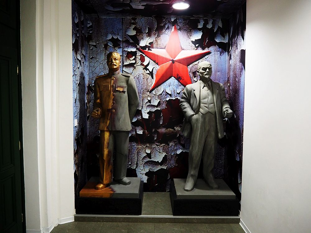 Two full-size statued in a niche in the wall: Stalin on the left in a military suit, Lenin on the right in a civilian suit. Both seem to be made of metal. The wall behind them has badly peeling paint and, in the middle, between the two statues, is a big red star.