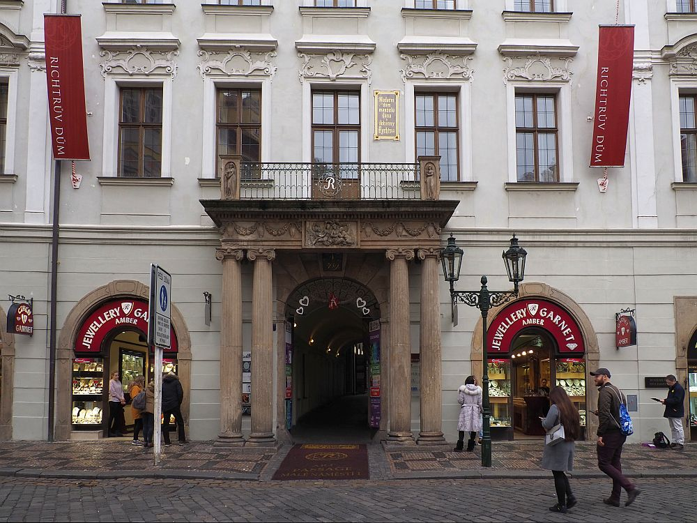 "A typical Prague building with ornate touches above the windows. In the center ground floor is a grand entrance with two pillars on either side supporting a balcony. On either side of the entrance are shops, both with a sign reading ""Jewellery Garnet"""