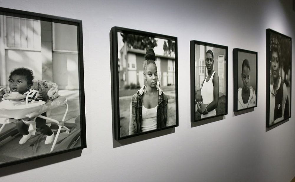Looking down a row of framed photographs: all in black and white and all portraits of African Americans. The furthest left is a baby in a walker, next four are all young women.
