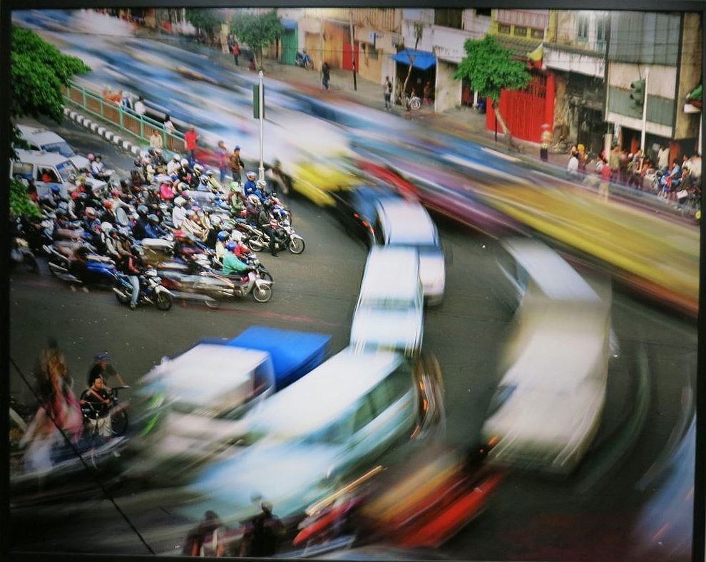 A cluster of scoooters stand still in the middle left. Top left to middle right and top left, curving around to bottom left: cars stream by, all blurry from motion. In the background: the shops along the street are also still.