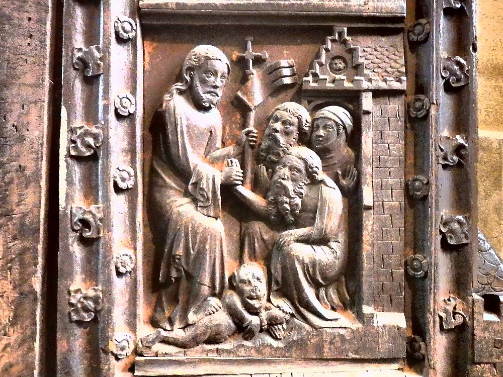 A bas-relief depicts a man on the left, standing, holding a staff with a cross on its top, with one foot on a chained creature - a dog? a devil? It's not clear. Two men and a woman huddle on the right, and the man on the left holds the hand of one of the men.