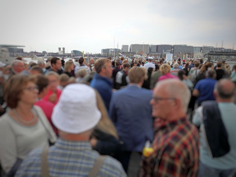 A crowd of people all standing and waiting. The dock is not visible in the background because of the crowd, but a group of apartment buildings are visible in the background.