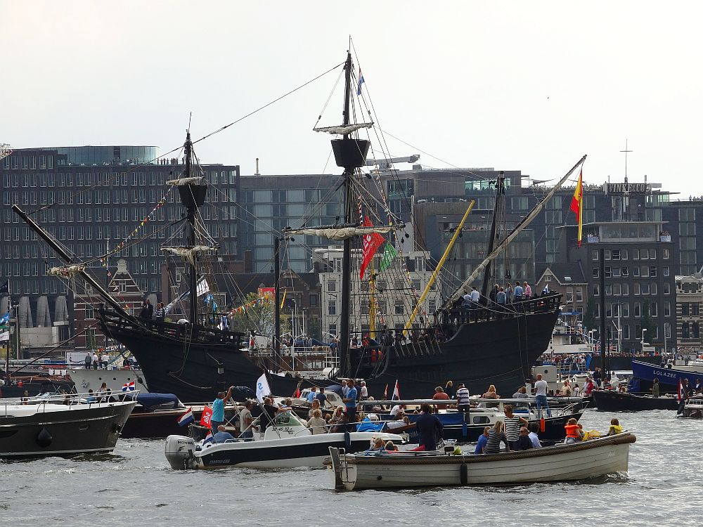 "Another general view. In the background, a row of modern apartment buildings. Moorred on the other side: another ship that looks like a pirate ship: black with a high bow and high stern, on which people are standing. It has two masts, each with a ""crow's nest"" on the top. In front of that, on the river, lots of small motorboats pass, crowded with passengers."