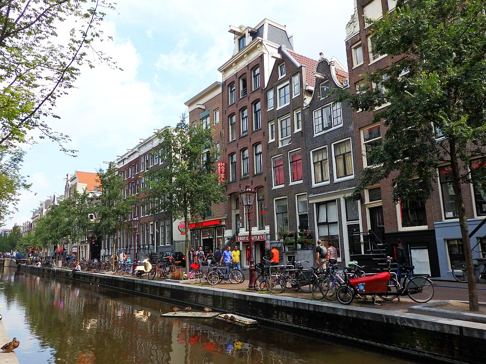 A row of typical Amsterdam canal houses along a canal: each has a different shaped gable, but all are red brick with big windows. Many bikes are parked along the canal edge and a few pedestrians walk along the street.