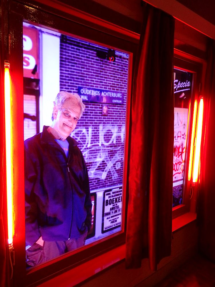 The two windows have red lights along their sides and heavy dark red curtains. They open on what looks like an alley and a man - grey hair, leering grin - stands looking in with his hands in his pockets.