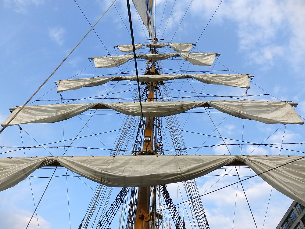 Looking up at a tall ship mast with five sails, furled on horizontal beams, one above the other.