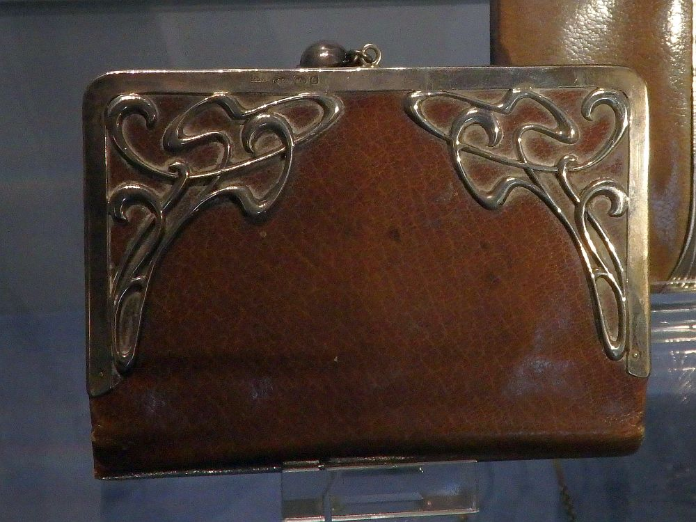 A smooth brown leather bag with a metal rim on the top and sides. The metal has art nouveau-style swirls in the top corners.