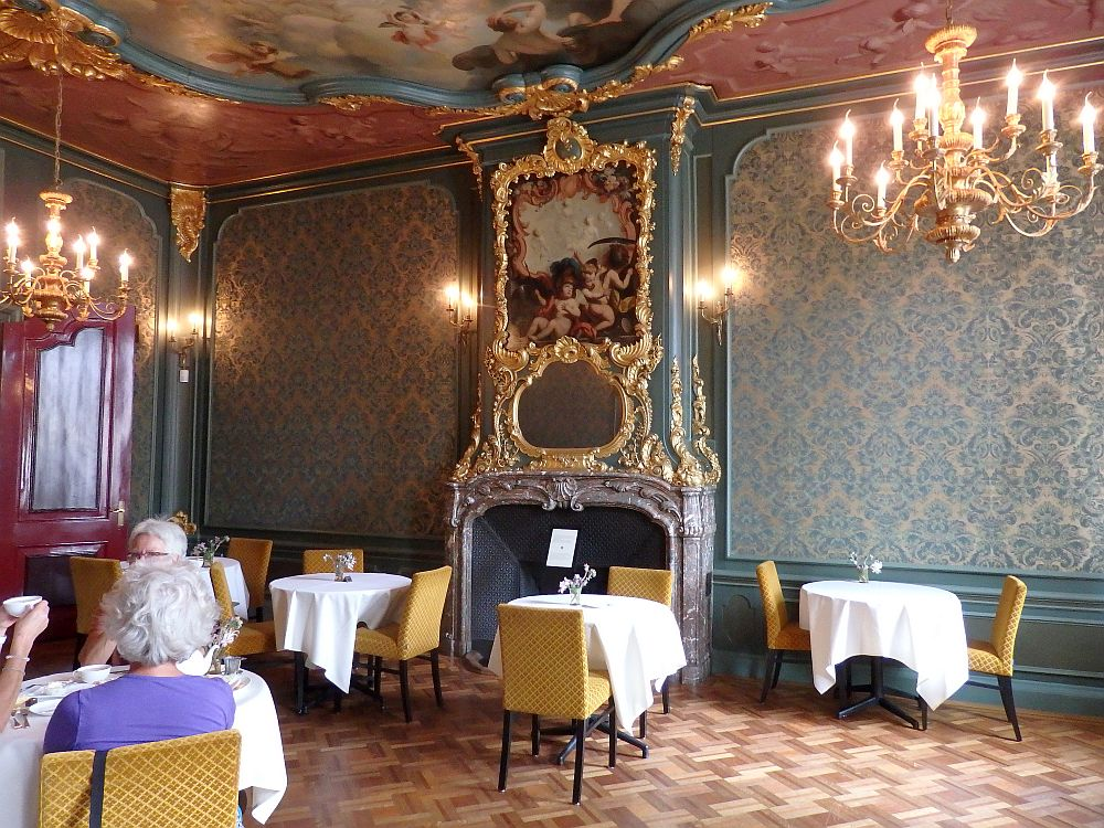 The room has a high ceiling, and the bit that is visible has a gilded inset frame with a baroque painting in it. The mantelpiece is also gilt-edged, and the gold extends around an oval mirror and a baroque painting above the mirror, with a gilt-framed crest of some sort above that. The walls are comparatively simple, with a blue-flowered wallpaper and a wainscoting below that. the floor is parquet and a few tables with tablecloths are scattered around. Three women sit at a table on the left.