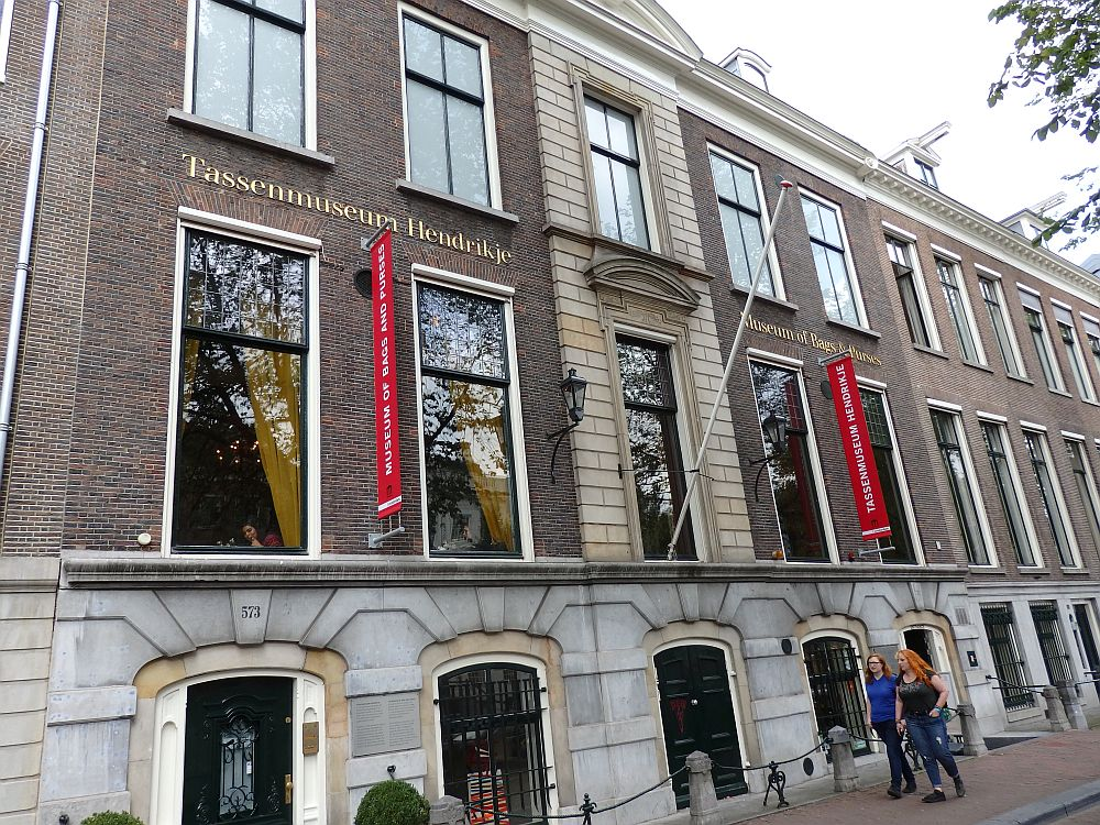 "The front of the museum is quite grand-looking: red brick with tall windows (smaller on the ground floor). Red banners extend from the facade advertising the museum. Two signs say ""Tassenmuseum Hendrikje"" and ""Museum of Bags and Purses"""
