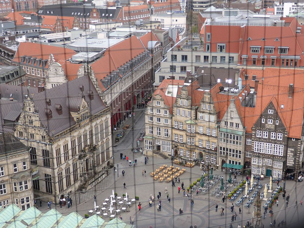 Looking down on an open square, with a row of historical buildings on one side, each with a stepped or pointed gable and many windows.