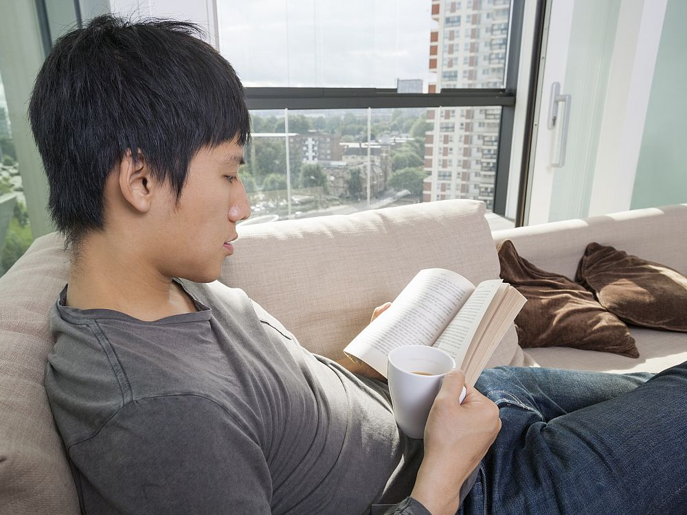A young Asian man relaxes on a white sofa reading a book and holding a cup of coffee. If he is travel-addicted it's a book about travel!