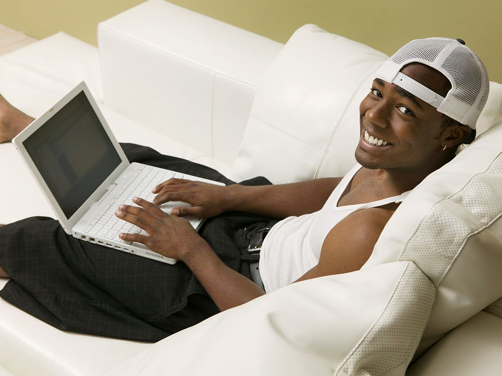A young black man stretches out on a white sofa. He wears a white cap set backwards on his head, a white t-shirt and black shorts. His hands are on a laptop but he is smiling at the camera.