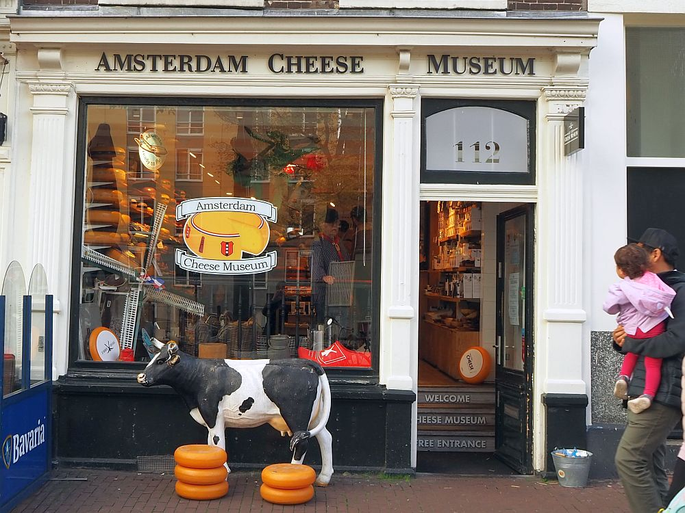 The storefront of the Amsterdam Cheese Museum. A big glass window with a wheel of cheese painted on it. In front of the store is a full size statue of a black and white cow, along will two piles of what I assume are plastic wheels of cheese.